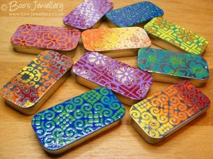 Enamel designs on stainless steel sliding lid pill boxes.