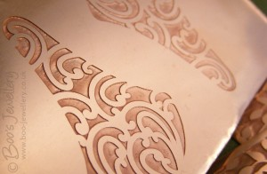 Newly etched raw copper design, ready for cutting into a pait of earrings.
