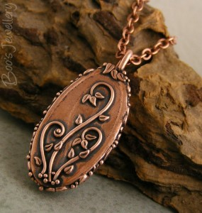 Back of the cabochon pendant, decorated with slender sinuous tendrils and tiny leaves.