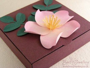 A paper wild rose with leaves, used here to decorate a shallow gift box for jewellery presentation.