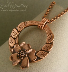Circle pendant made in copper clay with a wild rose centre piece with accompanying leaves.