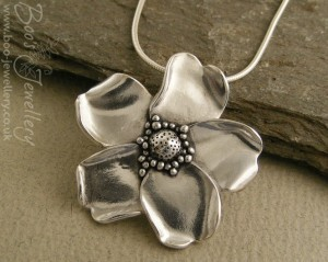 Hand sculpted wild rose pendant in pure silver.