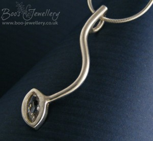 This hand crafted silver pendant features sleek lines and a gorgeous marquise shaped Cubic Zirconia stone.