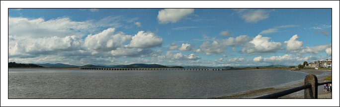The newly refurbished railway bridge crossing the bay at Arnside in Cumbria, in front of the hills of the Lake District.