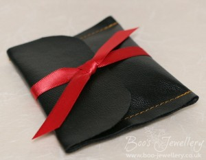 Black faux leather jewellery pouch with red double satin ribbon.