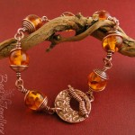 Faux amber spiral wrapped antiqued copper bracelet with a hand crafted toggle clasp.