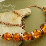 Faux amber and mobius ring antiqued copper necklace with a tapered beaded section with graduating sizes.