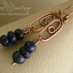 Elongated spiral link earrings with a stack of lapis rondelles.
