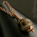 Antiqued copper and glass bead pendant with wire wrapped bail and hand crafted flower bead cap.