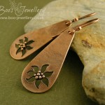 Teardrop earrings in pink bronze with poinsettia style flowers cut out and finished with tony rolled balls.