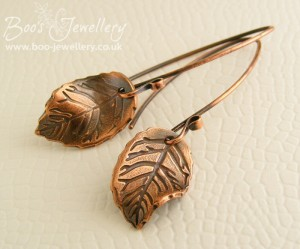 Antiqued copper contoured leaf earrings on feature earwires.