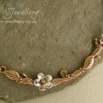 Twig necklace in pink bronze featuring riveted silver blossoms and a peridot green cubic zirconia gemstone.
