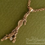Twig pendant, featuring hand crafted leaves, seed pods, tendrils and a tiny ladybird. Set with a cubic zirconia gemstone.