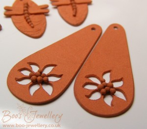 These Poinsettia style earrings were designed and cut with the Silhouette cutter from dry clay 2 cards thick, then tiny rolled balls separately appliqued. The dragonflies in the background had wings cut with a craft cutter.