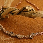 Twig necklace with tiny hand sculpted details, including leaves, tiny berries, seed pods, tendrils and even a tiny ladybird scampering along the twig. Made in Aussie Metal Clay medium fire superflex clay Desert Sun.