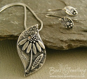 Fine silver daisy pendant with an inset cubic zirconium gemstone and matching earrings.