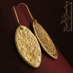 Gold bronze oval earrings with a reticulated texture, polished to a shine on the high spots.