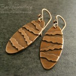 Oval earrings with torn edge appliqued stripes and scrolled hammered earwires.