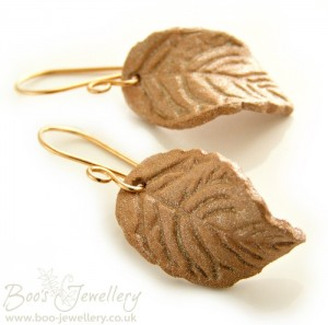 Air dry clay leaf earrings, varnished with a metallic shimmer and hung on bronze earwires.