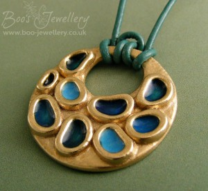 A gold bronze pendant with little softly shaped reservoirs filled with coloured resin.