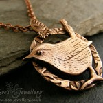 Hand sculpted pink bronze wren pendant with a delicate leaf bail.