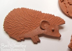 Hedgehog pin in dry metal clay before firing.