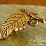 Sunny bronze leaf and twig brooch pin featuring a peridot coloured cubic zirconium gemstone.