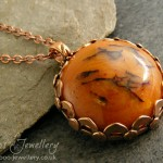 Faux Chinese amber cabochon set in a pink bronze bezel set pendant.