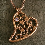 Filigree heart pendant made in a pink bronze metal clay and adorned with a lavender coloured cubic zirconium gemstone and tiny ivy leaves, tendrils, berries and leaves.