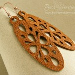 Earrings featuring a lightweight faux wood oval charm with a cut out geometric pattern. The large charms hang from balled antiqued copper earwires.