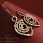 Darkly antiqued copper earrings each feature one single large leaf spiral of hammered copper wire.