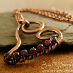 A new version of my curly heart pendant, wire wrapped with tiny faceted garnets.