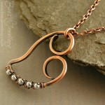 Smaller version of my antiqued copper curly heart pendant, wire wrapped with tiny silver beads.