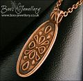 Oval copper pendant with hand drawn geometric design