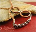 Curly copper heart pendant wrapped with silver beads