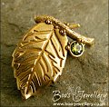 Bronze leaf brooch pin with peridot coloured gemstone