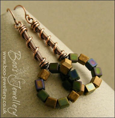 Coil on coil antiqued copper earrings with loop of glass cubes