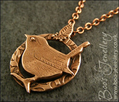Circle shaped pendant featuring a hand sculpted wren
