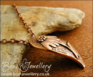 Wave shaped curvy copper pendant with relief daisy design