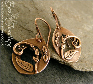 Teardrop shaped earrings featuring scrolls and leaves