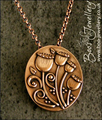 Oval pink bronze pendant featuring seed pods and scrolls