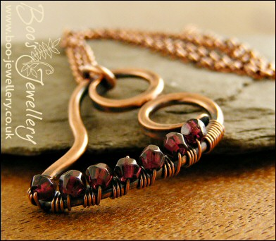 Curly heart pendant wire wrapped with faceted garnets